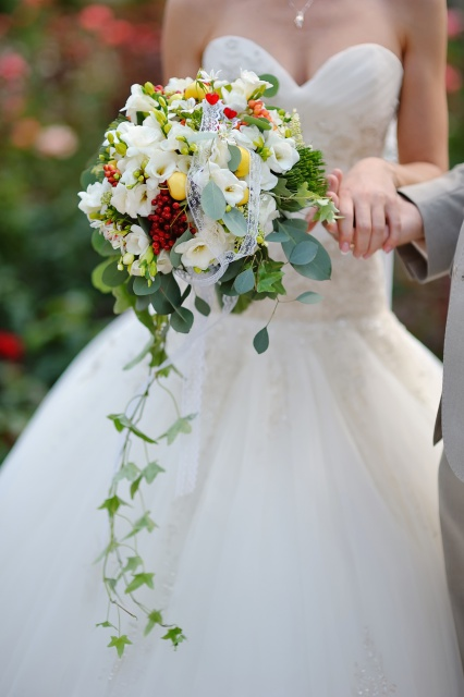 Bride holding wedding bouquet of colorful flowers and roses